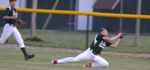 Wildcat senior Dakota Koehnke makes a play in the outfield against the Mt. Zion Braves when the teams split their doubleheader last week. Fellow senior Triston Holmes looks on.